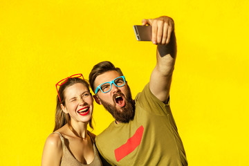 Hipsters couple macking selfie on yellow background