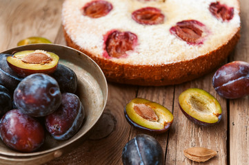 Pie with plum. In rustic style on a wooden surface