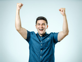 Portrait of happy young man raising his hands