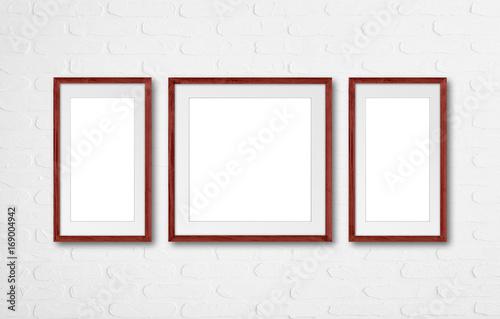 Three photo frames set on white bricks wall\