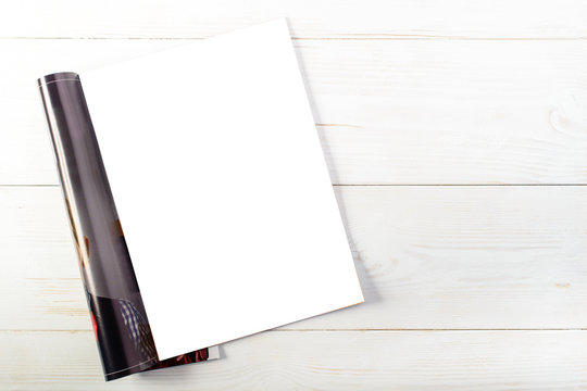 top view of open magazine with blank white pages on light wooden background, mock up for text. Ready for your new design and pattern