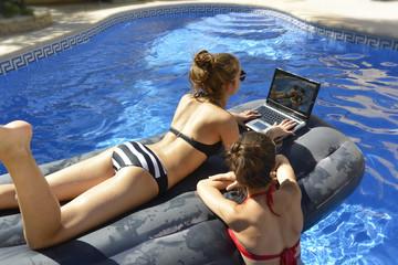 LAs chicas estan mirando las fotos en ordenador tumbados en la cama de aire en la piscina
