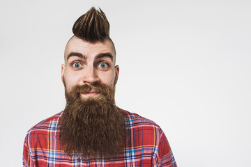 Young trendy man portrait. Excited punk man with Mohawk hairstyle. Isolated on gray background