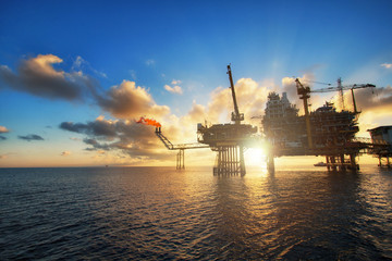 Silhouette,Offshore oil  platform in sunset or sunrise time. Construction of production process in the sea. Power energy of the world.