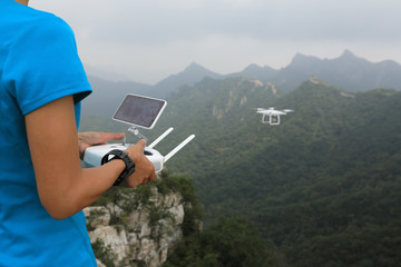 Printed roller blinds Khaki woman flying drone taking photo of the great wall landscape in China