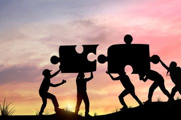 Silhouette people helping to connect jigsaw and puzzle to success, concept as improving and development business
