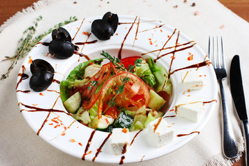 Greek salad in the white deep plate with the fork and knife