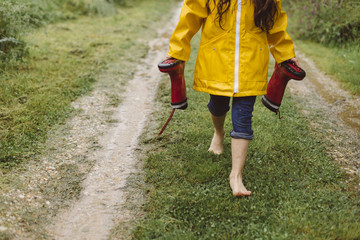 A barefoot child walking through a puddle.