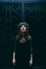 Woman wearing a flower crown and goth clothing