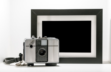 Vintage retro film camera with black and white picture frame isolated on white