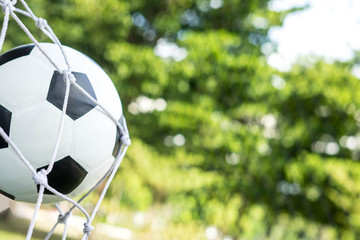 Soccer ball in goal net with green background