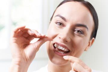 Woman  In Bathroom Flossing White Teeth