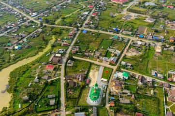 Perevalovo, Russia - August 22, 2017: Aerial view at Nicholas The Wonderworker church and rural area. Tyumen region