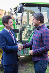 Farmer And Businessman Shaking Hands With Tractor In Background