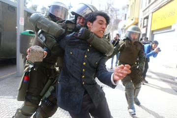 A demonstrator is detained during a rally to request changes in the education system in Santiago