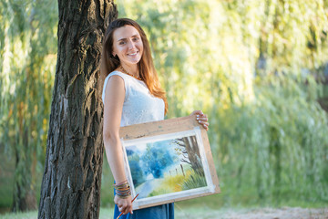 Portrait of charming female artist with picture and brush at the park