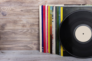 Retro styled image of a collection of old vinyl record lp's with sleeves on a wooden background....