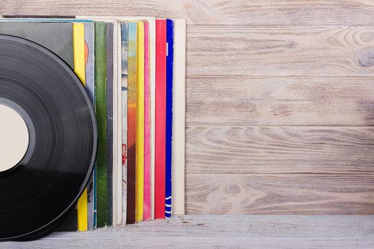 Vinyl records and headphones on table. Vintage vinyl disk