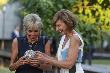 Carmen Iohannis, right, wife of Romania's President Klaus Iohannis, and Brigitte Macron, left, wife of French President Emmanuel Macron, observe a painted ostrich egg during a walk on the alleys of the Village Museum in Bucharest