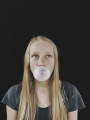 Teenage girl blowing bubble gum bubble