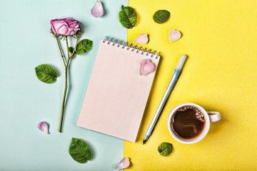 Style minimalism. Romantic image of a modern girl. A blank notebook page with a fresh rose, petals, a cup of coffee and a pen on a yellow and blue background.