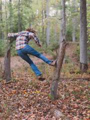 Guy jumping up and drop kicking a dead tree stump