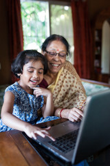 Little girl and her grandmother having fun while using laptop