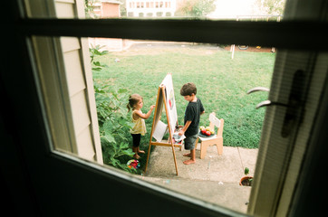 child painting on easle outside