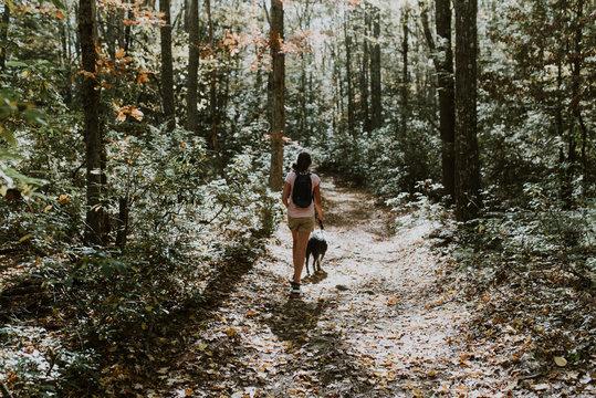 teen walking her dog in the woods
