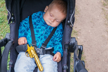 Sleeping baby with a gun in his hands