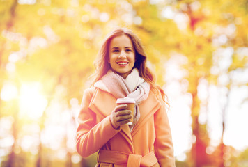 happy young woman drinking coffee in autumn park