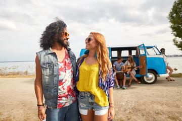 smiling young hippie friends near minivan car