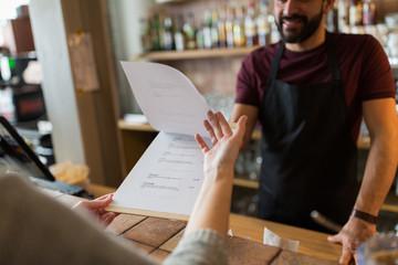 bartender and customer menu at bar