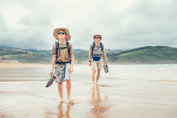 father and son backpacker traveler walk on sand ocean beach