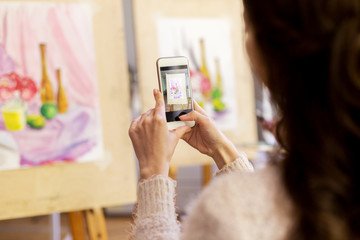 woman with painting on smartphone at art school
