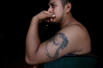 Man with a tattoo of Jesus Christ poses for a picture at the entrance of a bar in Ciudad Juarez