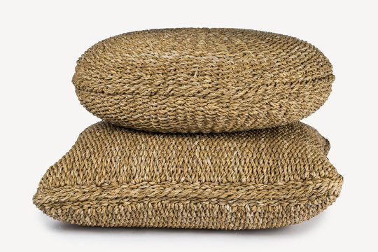 SET OF TWO LARGE RECTANGULAR AND ROUND NATURAL PLANT FIBRE BRAIDED DECORATIVE CUSHION POUF ON WHITE BACKGROUND