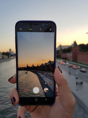 Female hand make a picture of city sunset on your smartphone . On the smartphone the low battery indicator.
