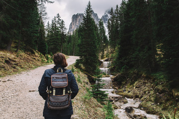 Woman traveler with backpack going to mountains