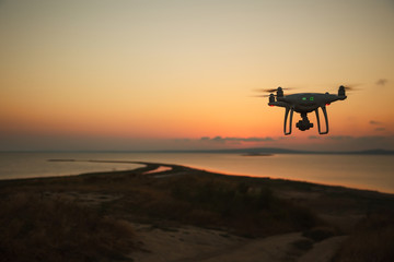 Drone flying at sunset over the sea. Drone in the air. Sunset photo frome the air.