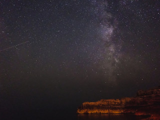 Milky way and shooting star over the cliff, long exposure image