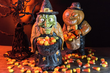 Halloween characters in spooky background collecting candy corn
