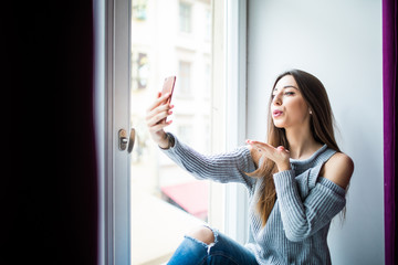 Side view of beautiful girl in casual clothes doing selfie using a smartphone and send kisses in video call while sitting on the window-sill at home