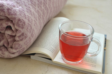 Cup of red tea over some books and a blanket in the background