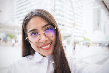 Pretty business woman take a self portrait with her smart phone outdoor, Asian nerdy glasses girl selfie with building background