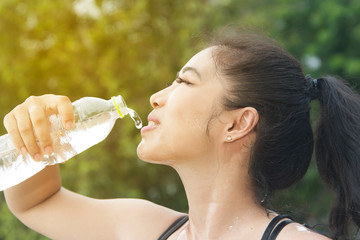 Sporty Asian woman drinking water outdoor after exercise.