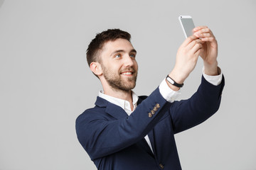 Business Concept - Portrait Handsome Business man take a selfie of himself with smartphone. White Background.