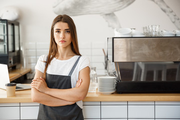 Coffee Business owner Concept - attractive young beautiful caucasian barista in apron with confident looking at camera in coffee shop counter.
