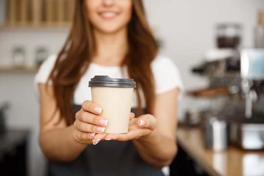 Coffee Business Concept - Beautiful Caucasian lady smiling at camera offers disposable take away hot coffee at the modern coffee shop