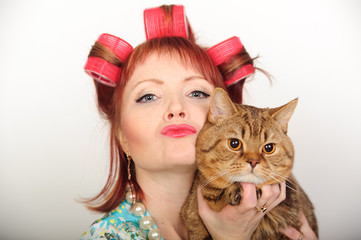 Housewife in curlers with a cat in her arms